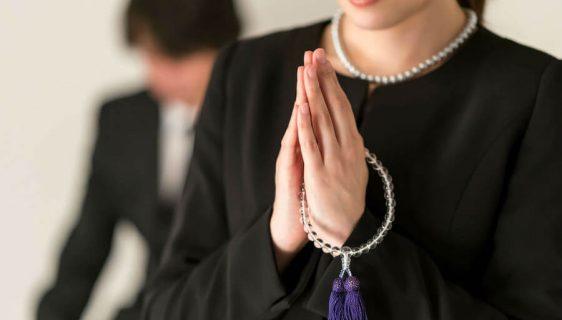 喪服を着て手を合わせる女性